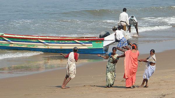 Local fishermen push their fishing boats ashore in Gokarna, Karnataka, India Photograph by Photo by Victor Ovies Arenas