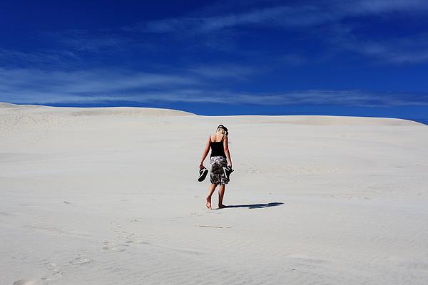 Lonely girl walking in sand dunes / desert Photograph by Pejft