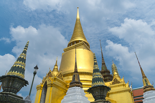 Low angle view of golden ornate temple spires, Bangkok, Thailand Photograph by John D. Buffington