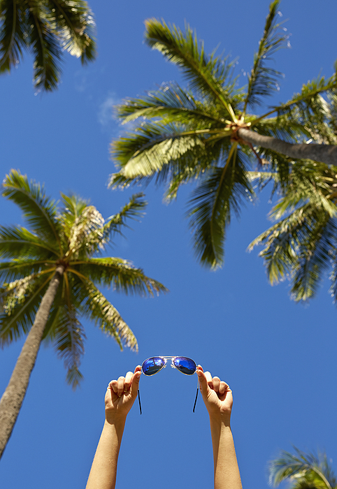 Low angle view of Pacific Islander woman holding sunglasses under palm trees Photograph by Colin Anderson Productions pty ltd