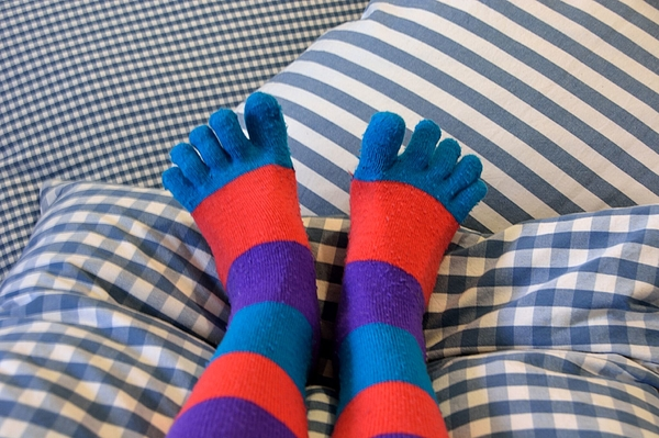 Low Section Of Person Wearing Colorful Socks On Bed Photograph by Alessandra Labate / EyeEm