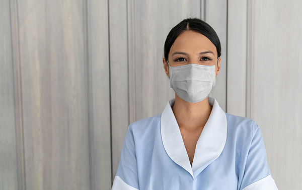 Maid wearing a facemask to avoid the spread of coronavirus while working at a hotel Photograph by Andresr