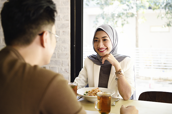 Malaysian man and woman having lunch in a restaurant Photograph by Carlina Teteris