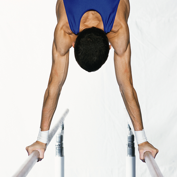 Male gymnast performing handstand on parallel bars, upper section, rear view. Photograph by Dominique Douieb