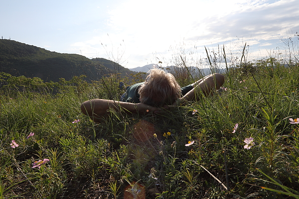 Male Hiker Relaxes In Meadow Above Distant Hills Photograph by Ascent/PKS Media Inc.