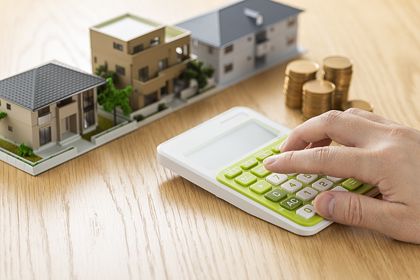 Man and house model calculating with calculator Photograph by Kuppa_rock