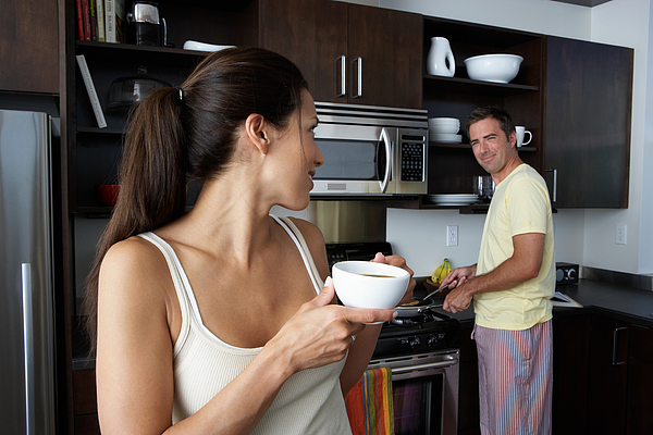 Man and woman preparing breakfast and smiling at one another Photograph by Thomas Northcut