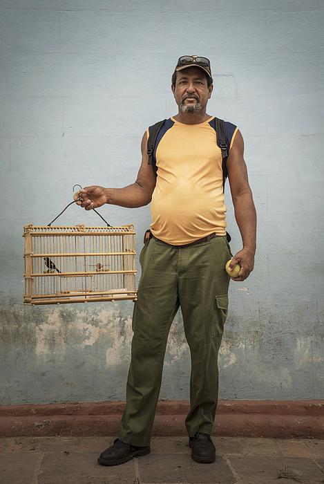 Man carrying caged pet bird Photograph by Buena Vista Images