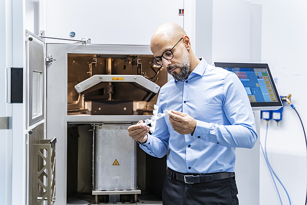 Man holding workpiece at 3d printer Photograph by Westend61