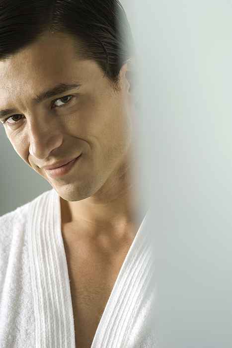 Man in bathrobe smiling at camera, portrait, cropped Photograph by PhotoAlto/Michele Constantini