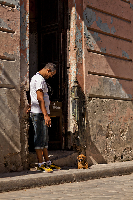 Man looking at dog in doorway Photograph by Merten Snijders