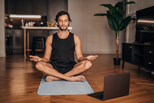 Man meditating in the living room Photograph by Hirurg