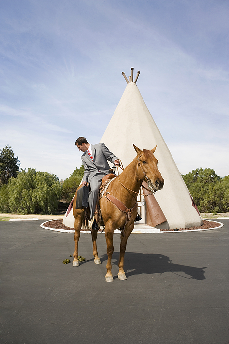 Man on horse in front of tepee-shaped motel unit. Photograph by David Zaitz