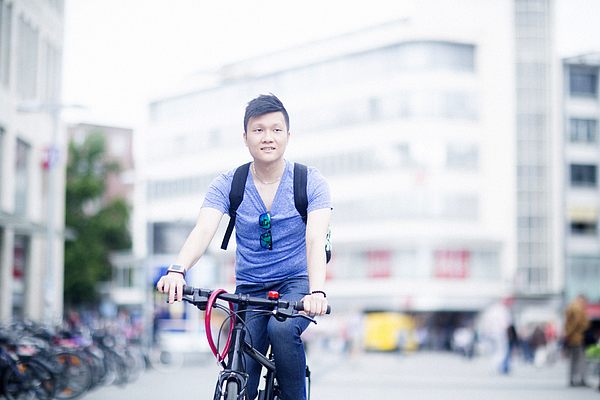 Man riding bicycle in city Photograph by Sigrid Gombert