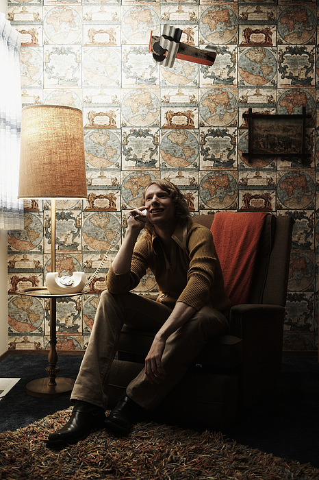 Man sitting in chair in room, talking on phone Photograph by Thomas Northcut