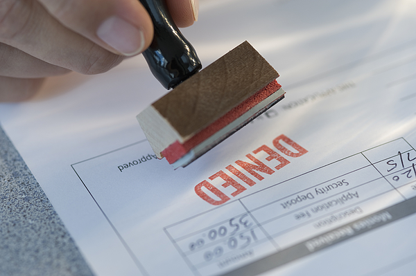 Man stamping denied on mortgage application Photograph by Tetra Images