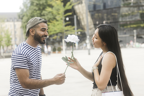Man standing in city square giving his girlfriend a white rose Photograph by Sigridgombert