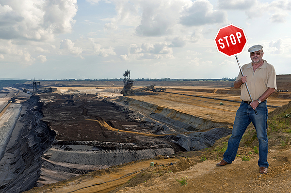 Man standing on the edge of an open pit, holding up a stop sign, Grevenbroich, North Rhine-Westphalia, Germany, Europe Photograph by Fhr