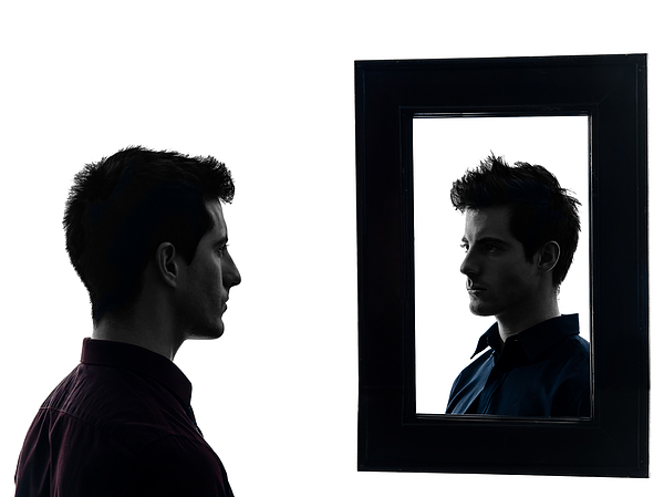 Man staring at his own reflection in mirror Photograph by Ostill