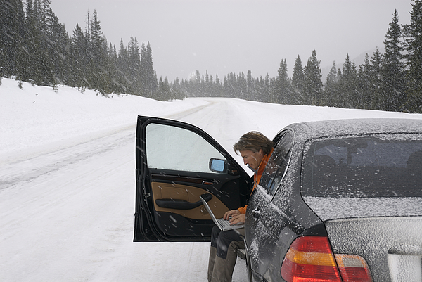 Man using computer to contact help in snowstorm Photograph by AscentXmedia