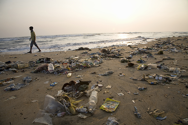 Man walking on a beach full of garbage Photograph by John Lund