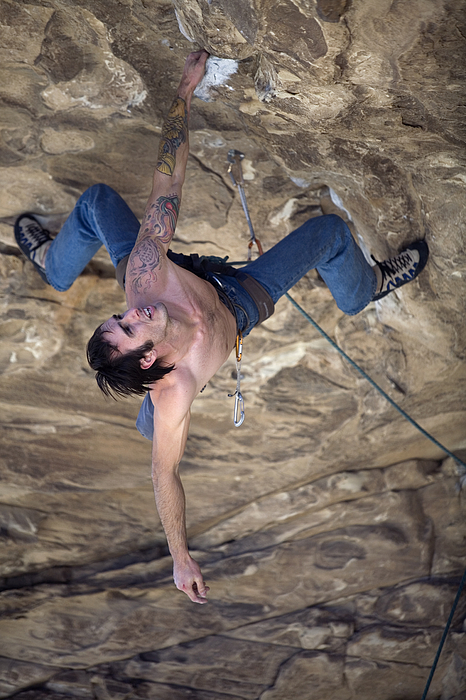 Man wearing blue jeans, without shirt, with tattoos hangs upside down from one arm while climbing an overhang. Photograph by Aaron Black