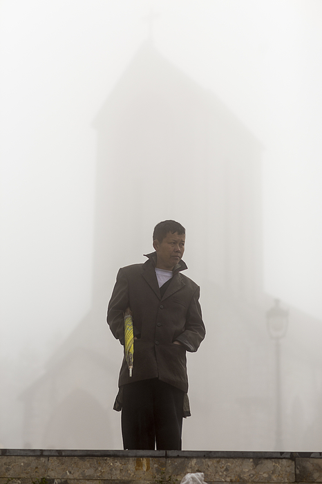Man with umbrella at misty church Photograph by Merten Snijders