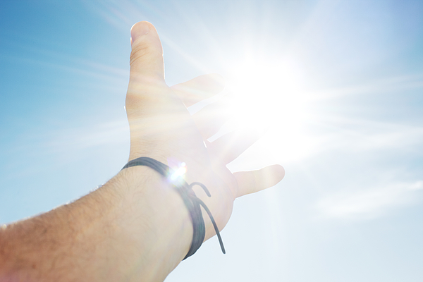 Mans hand reaching for sun Photograph by Hup