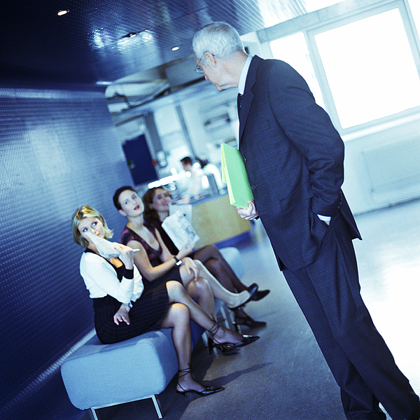 Mature Businessman Looking At Three Young Women. Photograph by Patrick Sheandell OCarroll