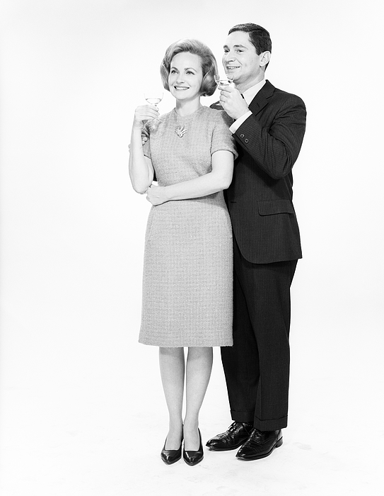 Mature couple drinking cocktails, studio shot Photograph by George Marks
