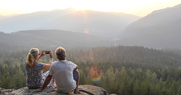 Mature couple relax on mountain ledge, look out to view Photograph by AscentXmedia
