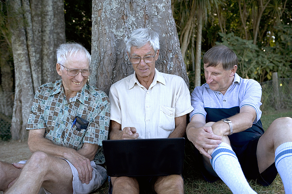 Mature man and senior men by tree, looking at laptop screen, smiling Photograph by Manchan