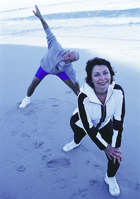 Mature Man And Woman Warming Up On Beach Photograph by Vincent Hazat