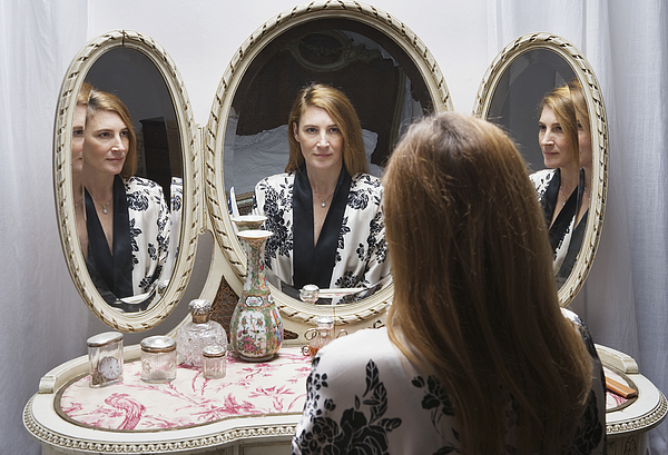 Mature woman looking at reflection in bedside mirror Photograph by Betsie Van der Meer