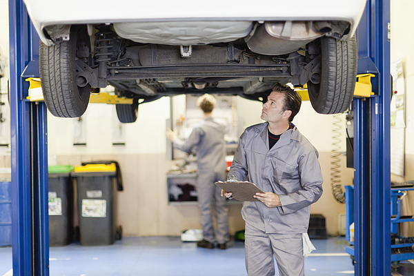 Mechanic examining underside of car Photograph by Photo_Concepts