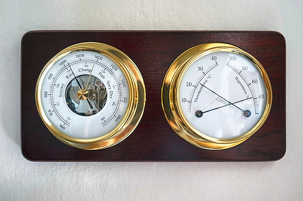 Mechanical weather station mounted on a wooden plate. Photograph by Emreturanphoto