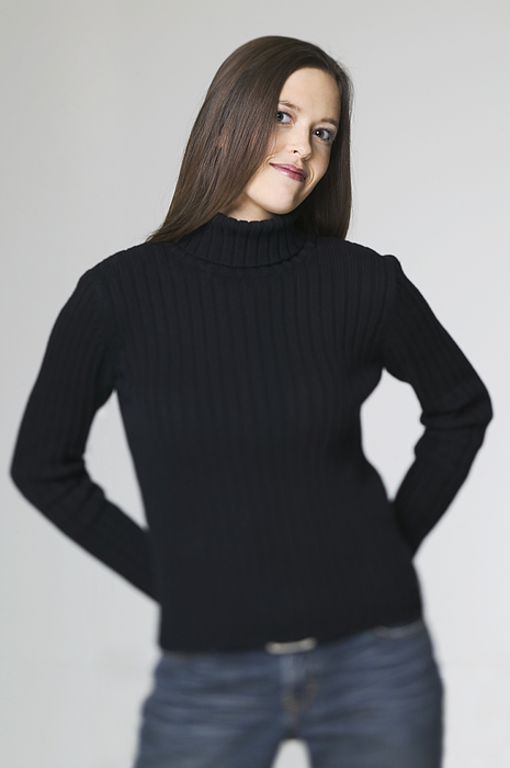 Medium Shot Of A Young Adult Woman In A Black Sweater As She Puts Her Hands On Her Hips And Smiles Photograph by Photodisc