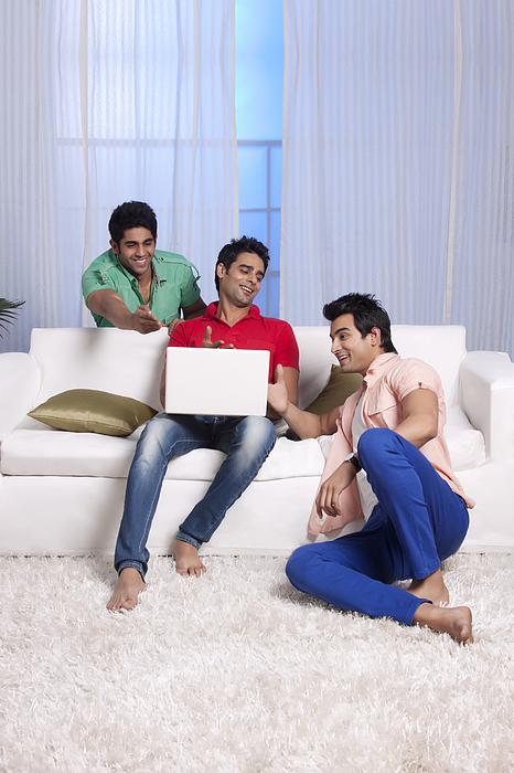 Men gesturing at their friends laptop Photograph by Sudipta Halder