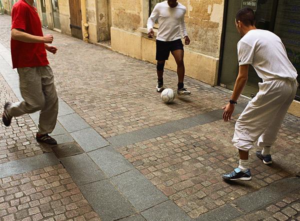 Men Kicking Soccer Ball In Street Photograph by Michael Mohr