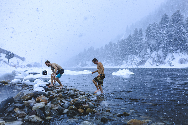 Men walking on stones in river during snowfall Photograph by Cavan Images