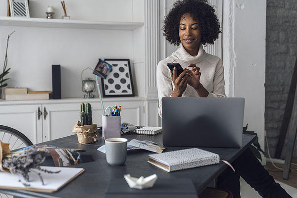 Mid adult woman working in her home office, using smartphone Photograph by Westend61