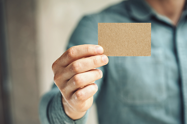 Mid-section of man holding business card Photograph by Sfio Cracho