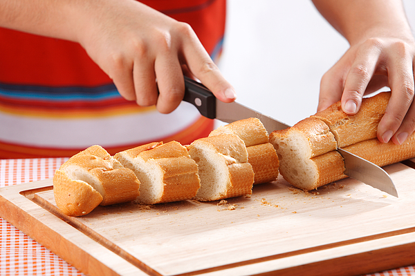 Midsection Of Man Cutting Loaf Of Bread On Table Photograph by Eskay Lim / EyeEm