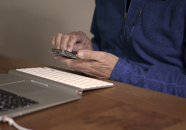 Midsection Of Man Using Mobile Phone By Laptop On Table Photograph by Paulien Tabak / EyeEm