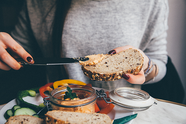 Midsection Of Woman Applying Spread On Bread At Home Photograph by Katarína Mittáková / EyeEm