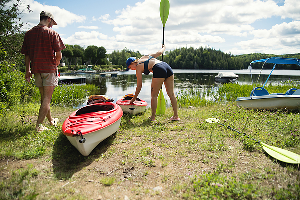 Millennial couple going kayaking on country lake. Photograph by Martinedoucet