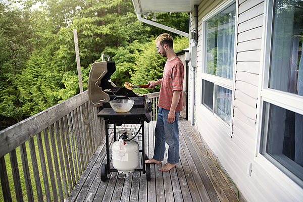 Millennial man cooking vegetables on barbecue in country house. Photograph by Martinedoucet