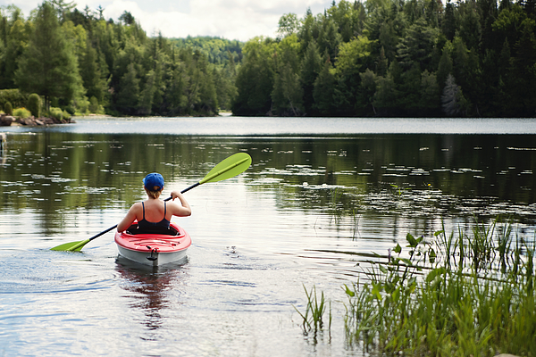 Millennial woman kayaking on country lake. Photograph by Martinedoucet