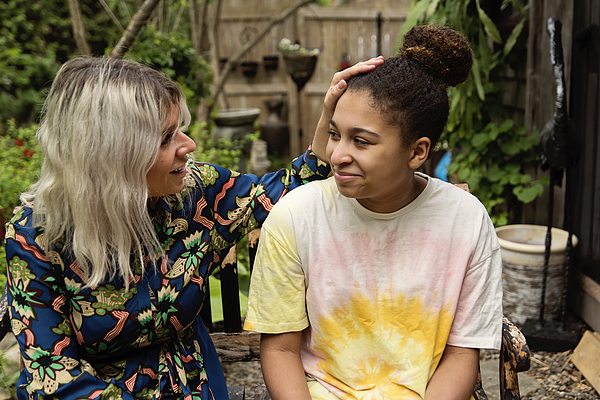 Mixed-race daughter and mother portrait in backyard. Photograph by Martinedoucet