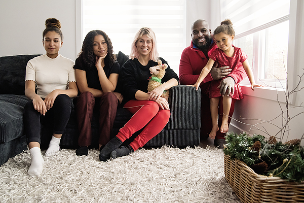 Mixed-race family portrait in living room. Photograph by Martinedoucet